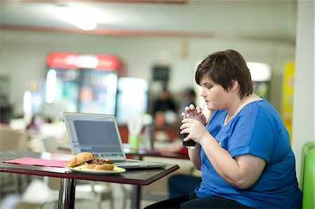 fat lady sitting - Young woman drinking coke in cafe Stock Photo - Premium Royalty-Free, Code: 649-07064045