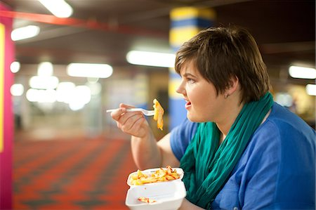 fat lady sitting - Young woman eating takeaway fries Stock Photo - Premium Royalty-Free, Code: 649-07064052
