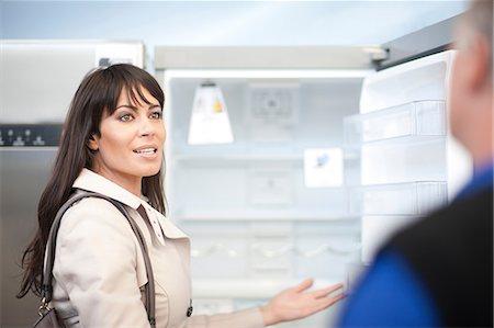 fridge - Woman looking at fridge in showroom Stock Photo - Premium Royalty-Free, Code: 649-07064064