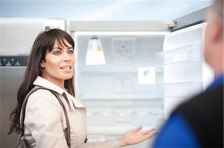 fridge - Woman looking at fridge in showroom Stock Photo - Premium Royalty-Free, Code: 649-07064064