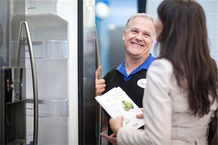 fridge - Salesman showing woman fridge in showroom Stock Photo - Premium Royalty-Free, Code: 649-07064065