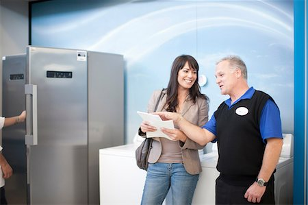 fridge - Woman negotiating with salesman in showroom Stock Photo - Premium Royalty-Free, Code: 649-07064060