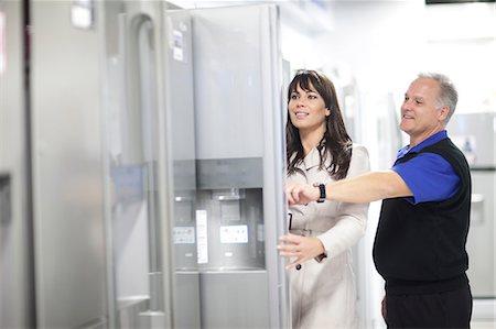 fridge - Woman looking at refrigerators in showroom Stock Photo - Premium Royalty-Free, Code: 649-07064078