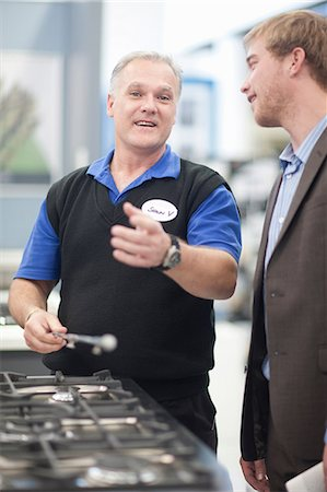 Young man negotiating with salesman in showroom Stock Photo - Premium Royalty-Free, Code: 649-07064070