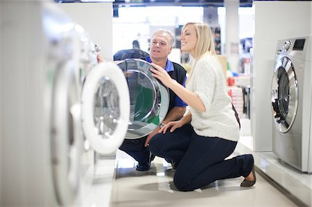purchase - Young woman and salesman looking at washing machines in showroom Stock Photo - Premium Royalty-Free, Code: 649-07064086