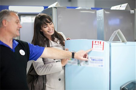 fridge - Woman looking at sale appliances in showroom Stock Photo - Premium Royalty-Free, Code: 649-07064081