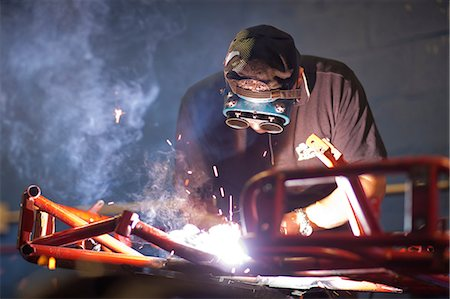 Mechanic welding go cart in workshop Stock Photo - Premium Royalty-Free, Code: 649-07064106