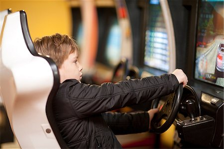 Boy playing on driving video game Stock Photo - Premium Royalty-Free, Code: 649-07064101
