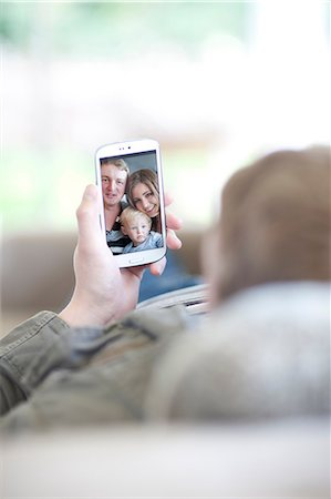 Man looking at family photo on cellphone Stock Photo - Premium Royalty-Free, Code: 649-07064189