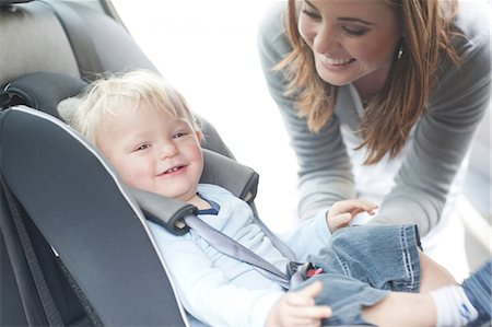 Mother checking baby son in back seat of car Stock Photo - Premium Royalty-Free, Code: 649-07064197