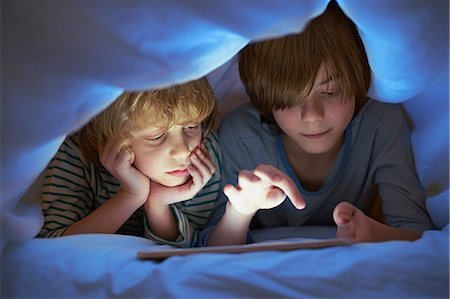 Brothers underneath duvet using digital tablet Stock Photo - Premium Royalty-Free, Code: 649-07064286