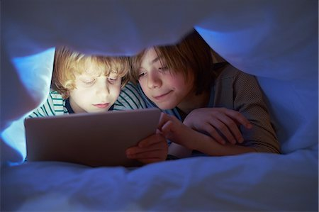 entertainment - Brothers underneath duvet using digital tablet Stock Photo - Premium Royalty-Free, Code: 649-07064287