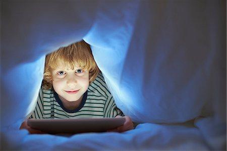 Boy underneath duvet using digital tablet Stock Photo - Premium Royalty-Free, Code: 649-07064288