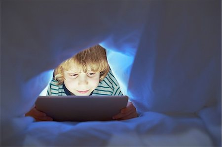 entertainment - Boy underneath duvet using digital tablet Stock Photo - Premium Royalty-Free, Code: 649-07064289