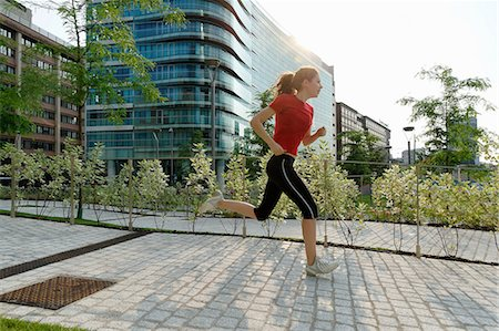Young woman running past office buildings Stock Photo - Premium Royalty-Free, Code: 649-07064318