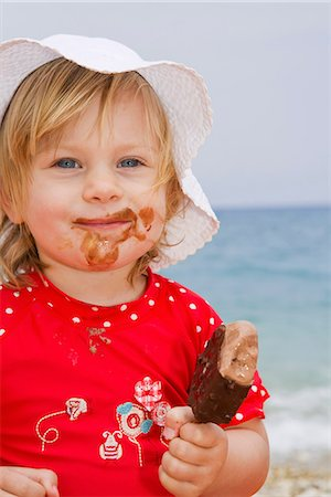 Baby girl eating ice cream on beach Stock Photo - Premium Royalty-Free, Code: 649-07064520