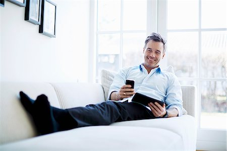 single mature people - Man relaxing on sofa using digital tablet and smartphone Stock Photo - Premium Royalty-Free, Code: 649-07064534