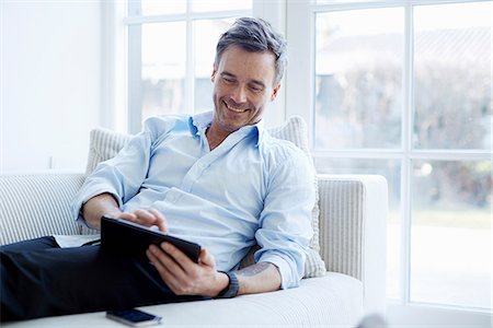Man relaxing on sofa using digital tablet Foto de stock - Sin royalties Premium, Código: 649-07064535