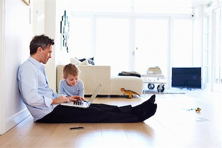 father with two sons not girls - Man sitting on floor using laptop, son watching Stock Photo - Premium Royalty-Free, Code: 649-07064556