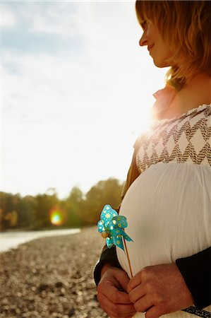 portrait of pregnant woman - Pregnant woman standing beside river holding windmill Stock Photo - Premium Royalty-Free, Code: 649-07064573