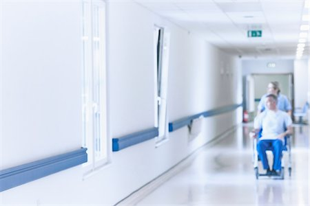 Nurse pushing patient in wheelchair down corridor Stock Photo - Premium Royalty-Free, Code: 649-07064708