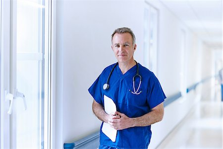 Doctor standing in corridor holding medical records Stock Photo - Premium Royalty-Free, Code: 649-07064714