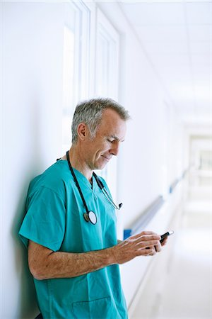 Surgeon standing in corridor looking at smartphone Stock Photo - Premium Royalty-Free, Code: 649-07064715