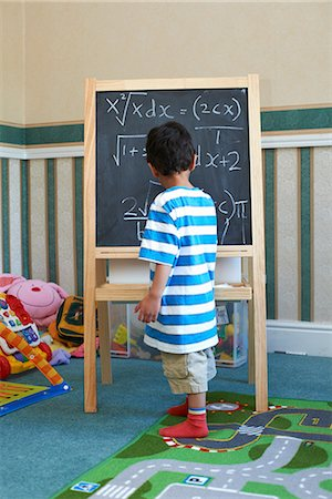 Boy standing beside blackboard with algebra Stock Photo - Premium Royalty-Free, Code: 649-07064776