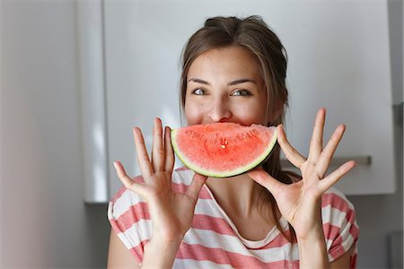 Woman covering mouth with slice of watermelon Stock Photo - Premium Royalty-Free, Code: 649-07064788