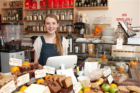 Young woman behind kitchen counter in cafe Stock Photo - Premium Royalty-Free, Code: 649-07064877