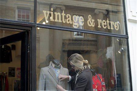 Woman putting jacket on shop dummy Stock Photo - Premium Royalty-Free, Code: 649-07064922