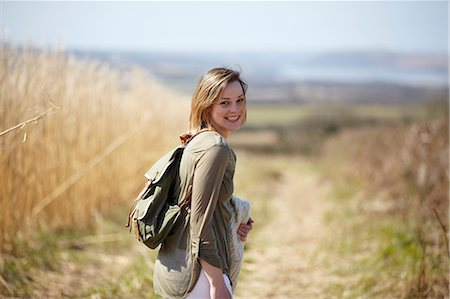 Portrait of young woman on dirt track next to field of reeds Stock Photo - Premium Royalty-Free, Code: 649-07063002