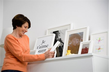 displaying - Senior woman looking at family photographs Stock Photo - Premium Royalty-Free, Code: 649-07063039