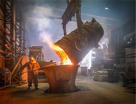 Steel worker and buckets of molten metal in steel foundry Stock Photo - Premium Royalty-Free, Code: 649-07063084