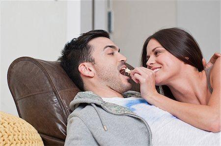 Young couple lying on sofa sharing popcorn Stock Photo - Premium Royalty-Free, Code: 649-07063110