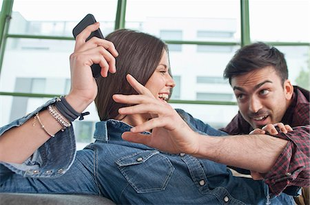 Young couple at home fooling about with mobile phone Stock Photo - Premium Royalty-Free, Code: 649-07063173