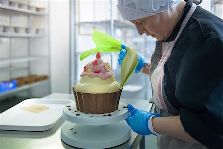 food processing plant - Chocolatier icing giant size cup cake Stock Photo - Premium Royalty-Free, Code: 649-07063206
