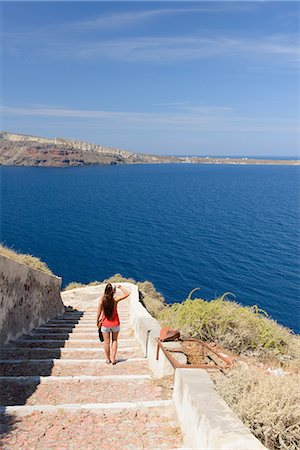 Female tourist walking down steps, Oia, Santorini, Greece Stock Photo - Premium Royalty-Free, Code: 649-07063225