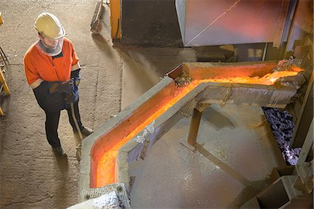 extremism - Worker monitoring molten metal at aluminum recycling plant Stock Photo - Premium Royalty-Free, Code: 649-07063374