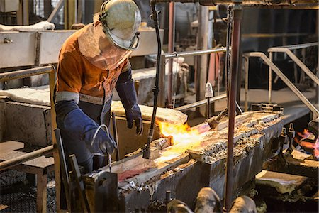 extremism - Worker testing molten metal at aluminum recycling plant Stock Photo - Premium Royalty-Free, Code: 649-07063375