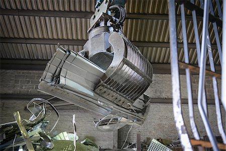 Excavator lifting scrap metal in warehouse Stock Photo - Premium Royalty-Free, Code: 649-07063371