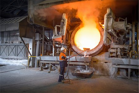 extremism - Worker raking liquid aluminum from furnace at recycling plant Stock Photo - Premium Royalty-Free, Code: 649-07063384