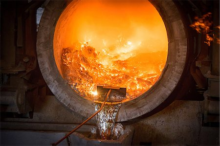 extremism - Raking liquid aluminum from furnace at recycling plant Stock Photo - Premium Royalty-Free, Code: 649-07063385