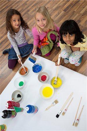 Portrait of three girls painting on floor Stock Photo - Premium Royalty-Free, Code: 649-07063432