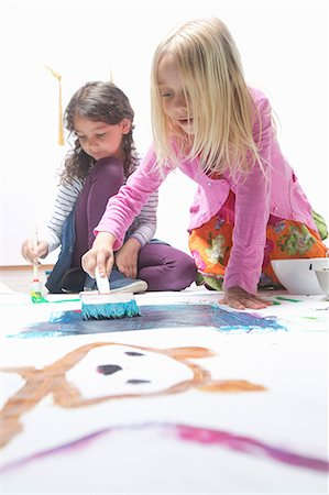 focus on background - Two girls painting on floor Stock Photo - Premium Royalty-Free, Code: 649-07063443