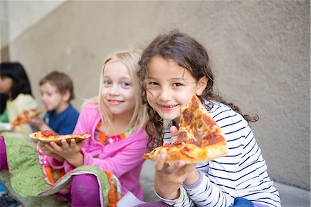 Small group of children eating pizza outdoors Stock Photo - Premium Royalty-Free, Code: 649-07063452