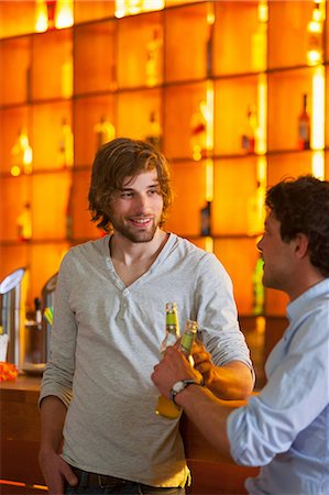 Two men standing at bar with bottles of beer Stock Photo - Premium Royalty-Free, Code: 649-07063515