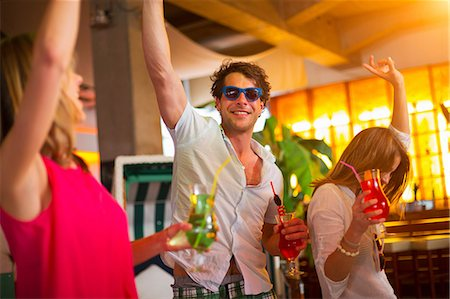Group of friends dancing with cocktails in bar Stock Photo - Premium Royalty-Free, Code: 649-07063535