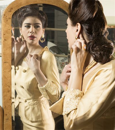 Close up of woman in vintage clothes looking in mirror Stock Photo - Premium Royalty-Free, Code: 649-07063575