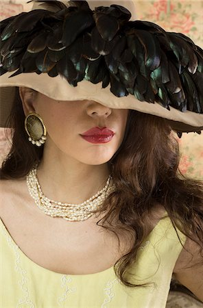 Woman in wide brimmed hat with feathers Stock Photo - Premium Royalty-Free, Code: 649-07063584